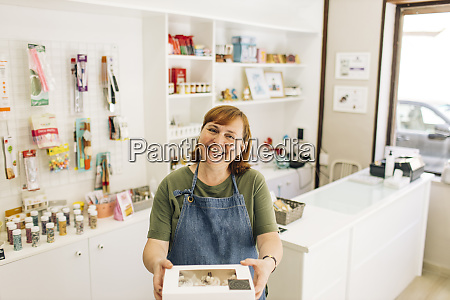 smiling female baker delivering cupcake box