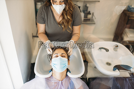 woman with mask getting hair washed