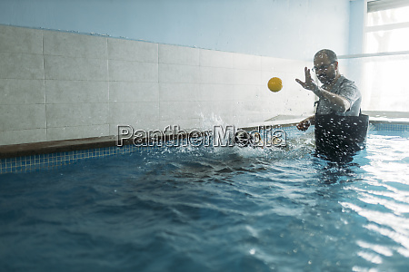 male physiotherapist throwing ball towards border