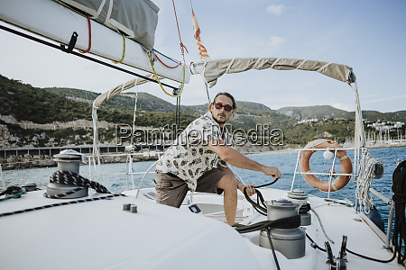 male sailor maneuvering with winch in
