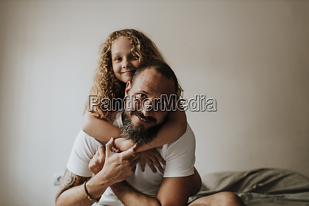father piggybacking daughter on bed at