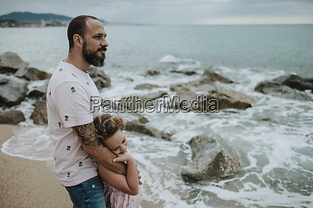 daughter leaning head on fathers hand
