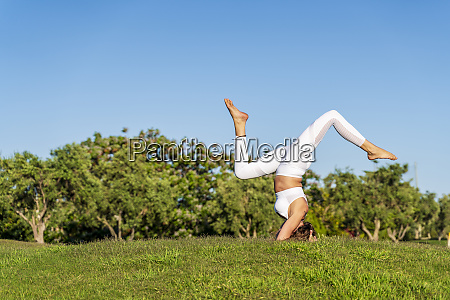 woman practicing yoga on lawn in
