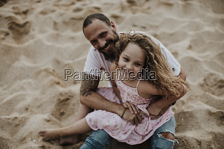daughter sitting on fathers lap while