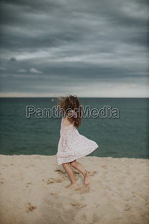 carefree girl dancing on sand against