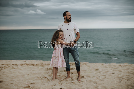 daughter embracing father at beach