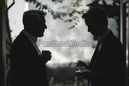 silhouette of two businessmen drinking coffee