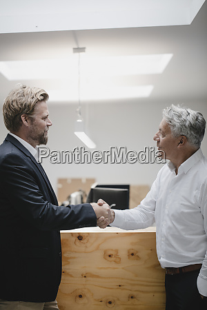 business partners standing in office shaking
