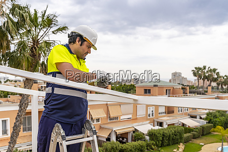mature male technician installing solar panel