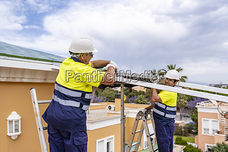 male coworkers installing solar panels on