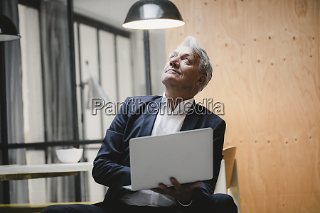 senior businessman sitting under ceiling lamp