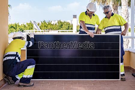 male technicians measuring solar panel in