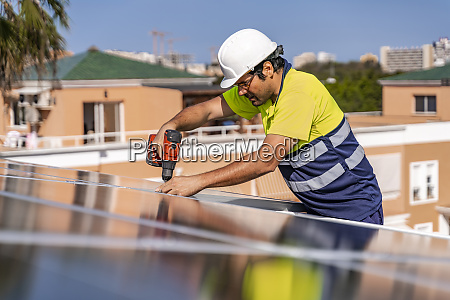 mature technician installing solar panel with