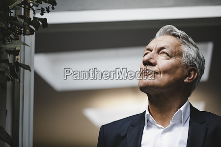 successful businessman looking up in satisfaction