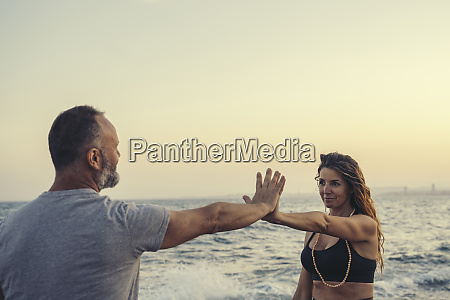 mature couple touching hands at beach