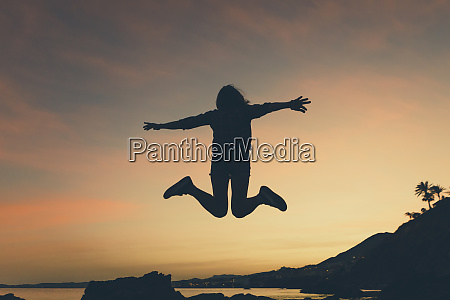 silhouette of jumping woman at beach