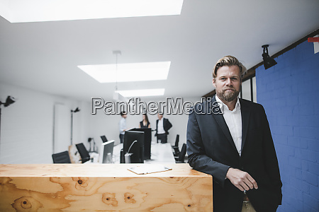 businessman leaning on counter coworkers working