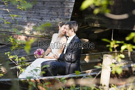 smiling, newlywed, couple, romancing, while, sitting - 28747038