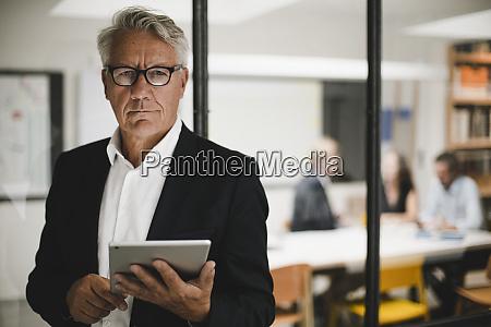 senior businessman using digital tablet coworkers