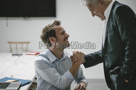 senior businessman shakinhg hands of younger