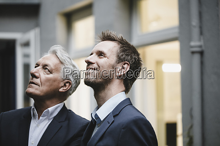 two successful businessmen looking at up