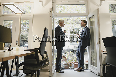 two businessmen standing in office drinking