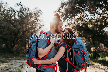 couple with backpacks kissing on a