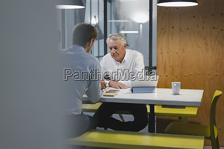 two businessmen sitting in office working