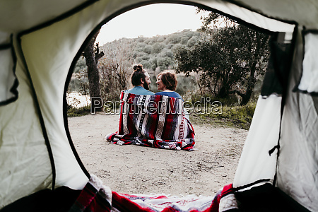 couple wrapped in a blanket camping