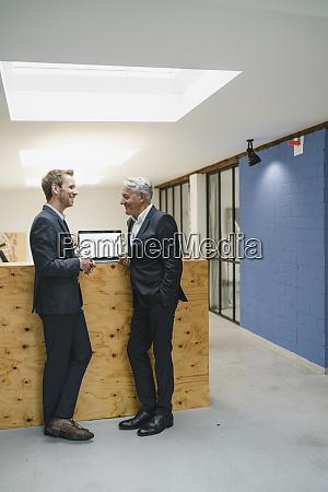 two businessmen stbding in office talking