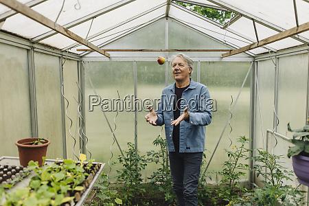 senior man in a greenhouse throwing