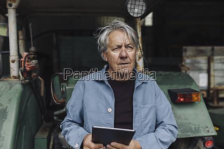 senior man holding tablet on a