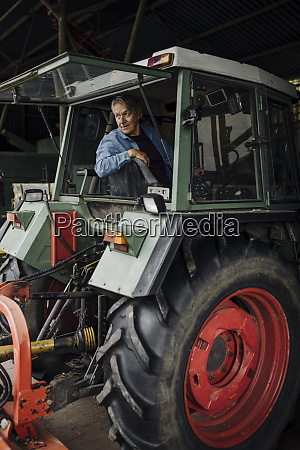 senior man driving tractor on a