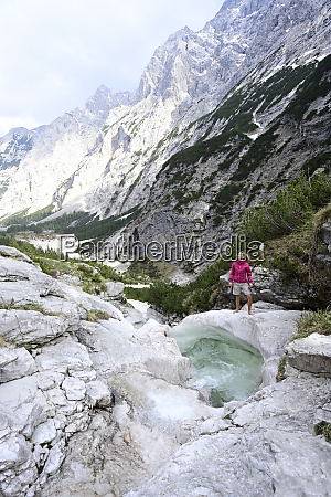 woman exploring while standing on rock