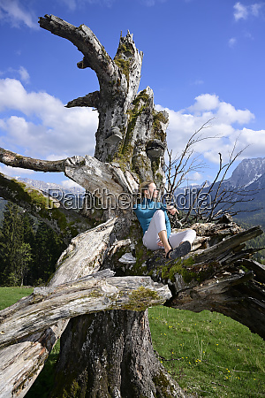 relaxed woman sitting on dead tree