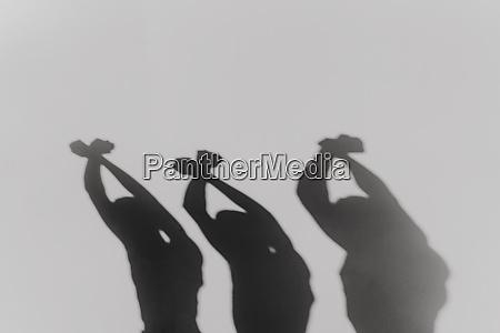 three man crossing hands and raising