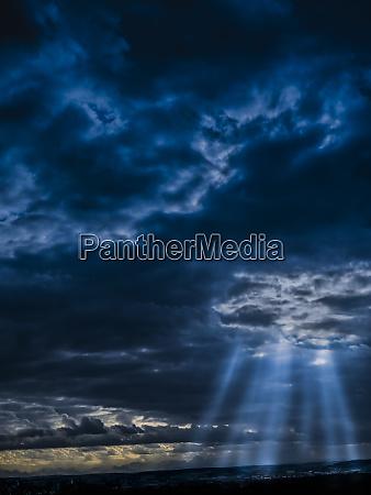 sunlight piercing through dark storm clouds