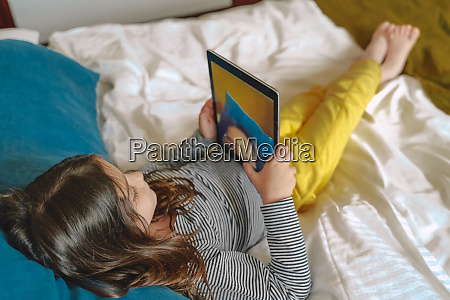 girl taking selfie with tablet lying