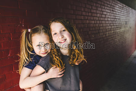 cute girl embracing sister while standing