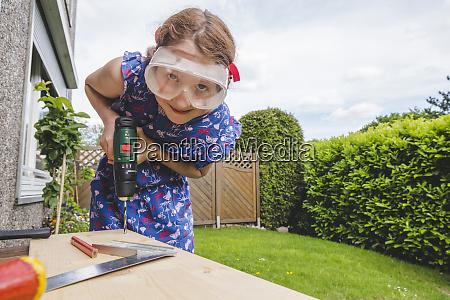 girl wearing eyewear drilling on plank