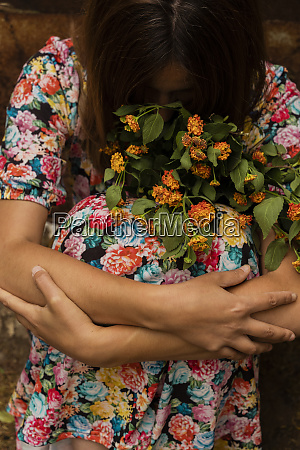sad woman holding orange flowers
