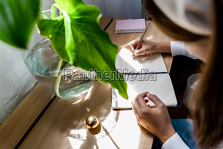 woman drawing in diary at desk