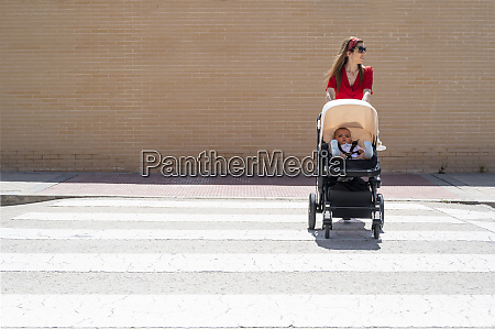 mother wearing sunglasses pushing son in
