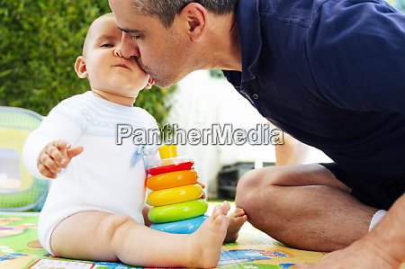 father kissing cute son playing with
