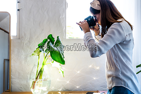 female photographer photographing plant in glass