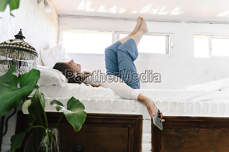 smiling woman lying on bed listening