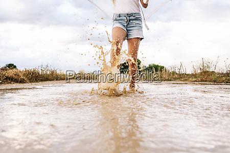 girl splashing water in puddle against