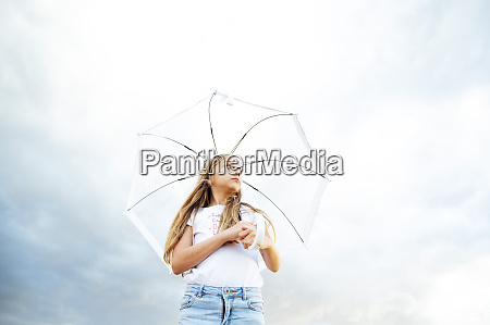 girl holding umbrella while standing against