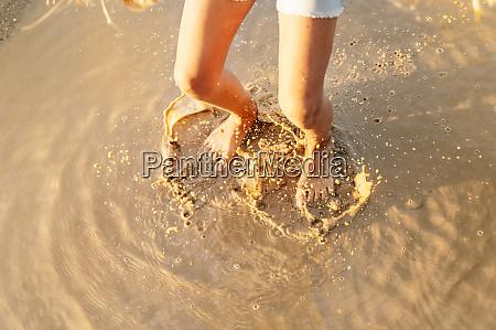 girl splashing water on puddle while
