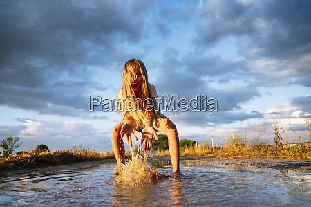 cheerful blond girl playing while splashing
